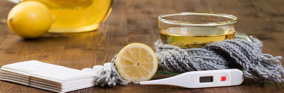 Verschiedene Erkältungsmittel liegen auf einem Holztisch, u.a. ein Fieberthermometer, heiße Zitrone, Taschentücher