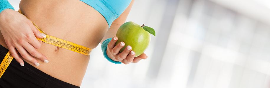Frau mit Apfel in der Hand und Massband um die Taille