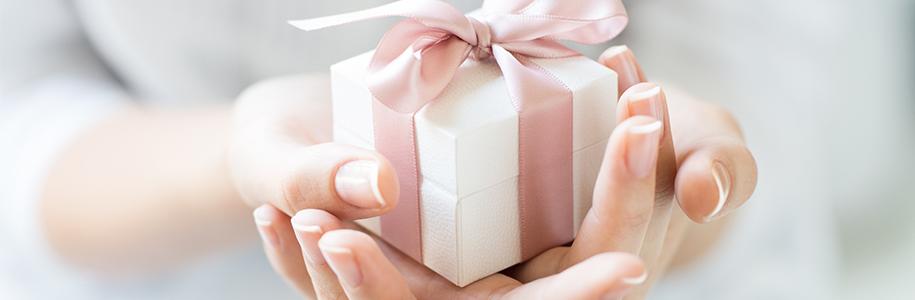 Frau die ein kleines Geschenk in den Händen hält