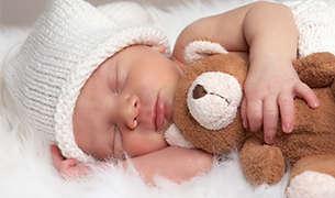Kategorie Babypflege - Ein schlafendes Baby mit Bär im Arm