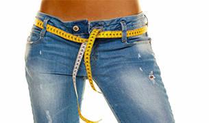 Kategorie Diätprodukte - Eine Jeans mit einem Massband als Gürtel