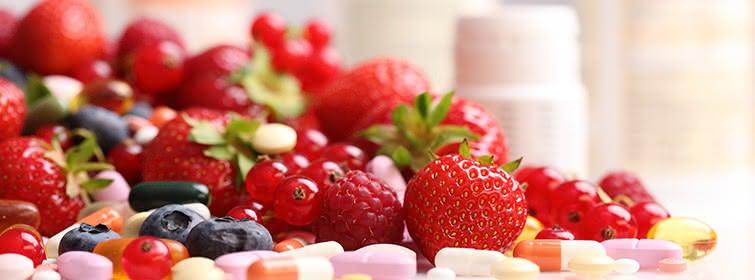Erdbeeren, Himbeeren, Johannisbeeren und Blaubeeren auf einem Haufen, davor Vitamintabletten